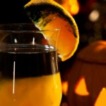 Closeup of Rotten Pumpkin Cocktail, black vodka, orange juice - Halloween drinks series